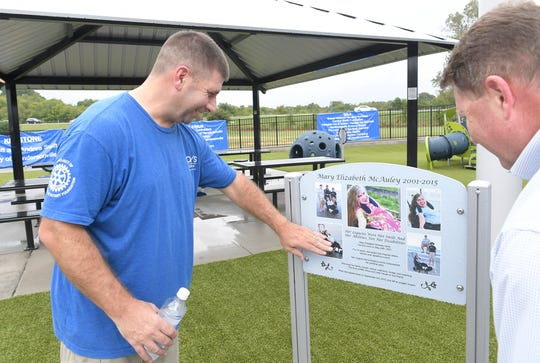 Tommy McAuley looks at photographs of his daughter, Mary, during the grand opening of Mary's Magical Place, an all-inclusive playground in Hendersonville, on Tuesday, Sept. 25, 2018.  Mary's Magical Place is named for Mary McAuley, a Hendersonville teen who died from complications of cerebral palsy in 2015.