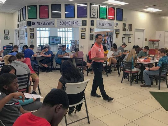 Kraig Feighery, founder and president of Alico Family Golf, teaches STEM students about the golf business Tuesday in Fort Myers.