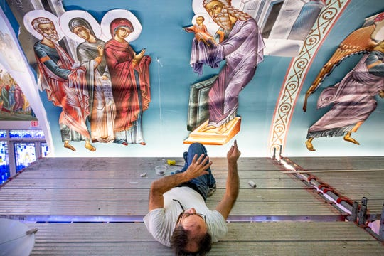 John Filippakis, a lifelong Byzantine icon painter, lies on his back to get a better perspective as he adds new iconography to the sanctuary of St. Paul Orthodox Church in Naples on Wednesday, Sept. 26, 2018.