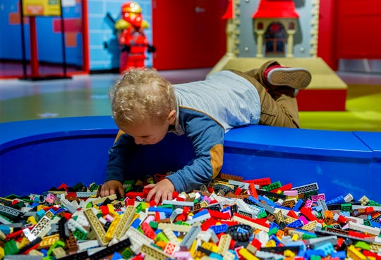 Wyatt Ginter, 2, of Columbus balances on the edge of a LEGO pit at LEGOLAND Discovery Center Columbus, during a preview event before the grand opening Friday, September 28.