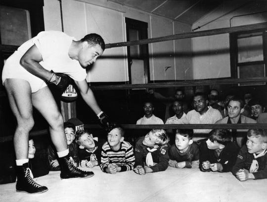 September 1950:  US boxer Joe Louis (1914 - 1981), in training at Pompton Lakes, New Jersey, for a match against Ezzard Charles, gently taps one of the watching youngsters.  (Photo by Keystone/Getty Images)