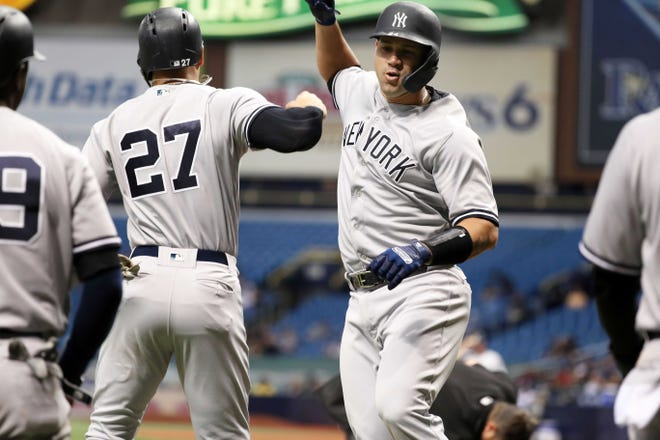 Sep 25, 2018; St. Petersburg, FL, USA; New York Yankees catcher Gary Sanchez (24) is congratulated by designated hitter Giancarlo Stanton (27) as he hits a 3-run home run during the third inning against the Tampa Bay Rays at Tropicana Field.