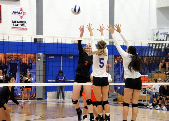 Artesia's Malori McSpadden (8) goes for a spike against Carlsbad's Alexa Sowers (5) during Tuesday's match. Artesia won in straight sets.