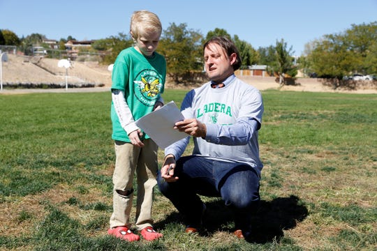 New Mexico Education Secretary Christopher Ruszkowski, right, signs his notes for fourth-grade student Tristen Rivera during a visit to Ladra del Norte Elementary School on Wednesday in Farmington.