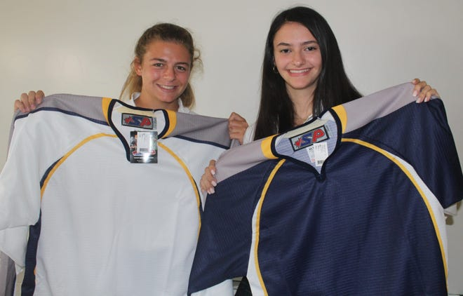 Maelyn Thayer (left) and Adrianna Rugiero, a pair of former Livonia Ladywood hockey players, proudly display the jerseys they will be wearing this year at the Academy of the Sacred Heart in Bloomfield Hills.