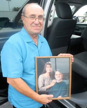 Tony Massa holds a photo of his daughter Michelle and son Mark.
