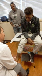 Dr. Jefferey Michaelson talks with Novi football player Jason Jennings Jr. and his dad, Jason Jennings Sr.