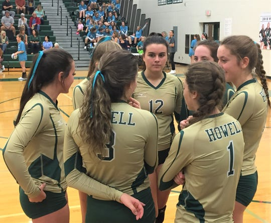 Howell players huddle up prior to the third set in a KLAA West match at Novi.