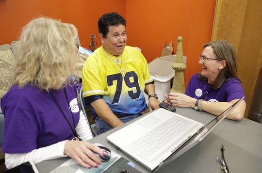 Charlotte Goska of the Coalition of Voting Organizations of Brown County (COVO) helps Antonio Vargas of Green Bay with his questions about getting registered to vote Tuesday, September 25, 2018 at a voter registration rally at the YWCA  in Green Bay, Wis. At left is COVO volunteer Debbie Kadon.