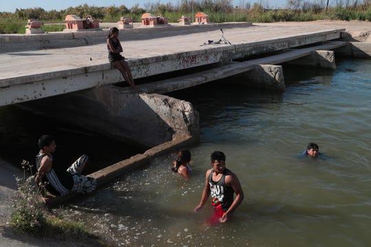 """Varios jóvenes nadan en el Canal Pacífico en Mexicali. Sus padres trabajan como """"pepenadores"""", o pizcadores de basura, en un depósito de basura cercano."""