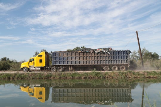 Un camión transita a lo largo del Canal Pacífico hacia un depósito de basura en Mexicali.