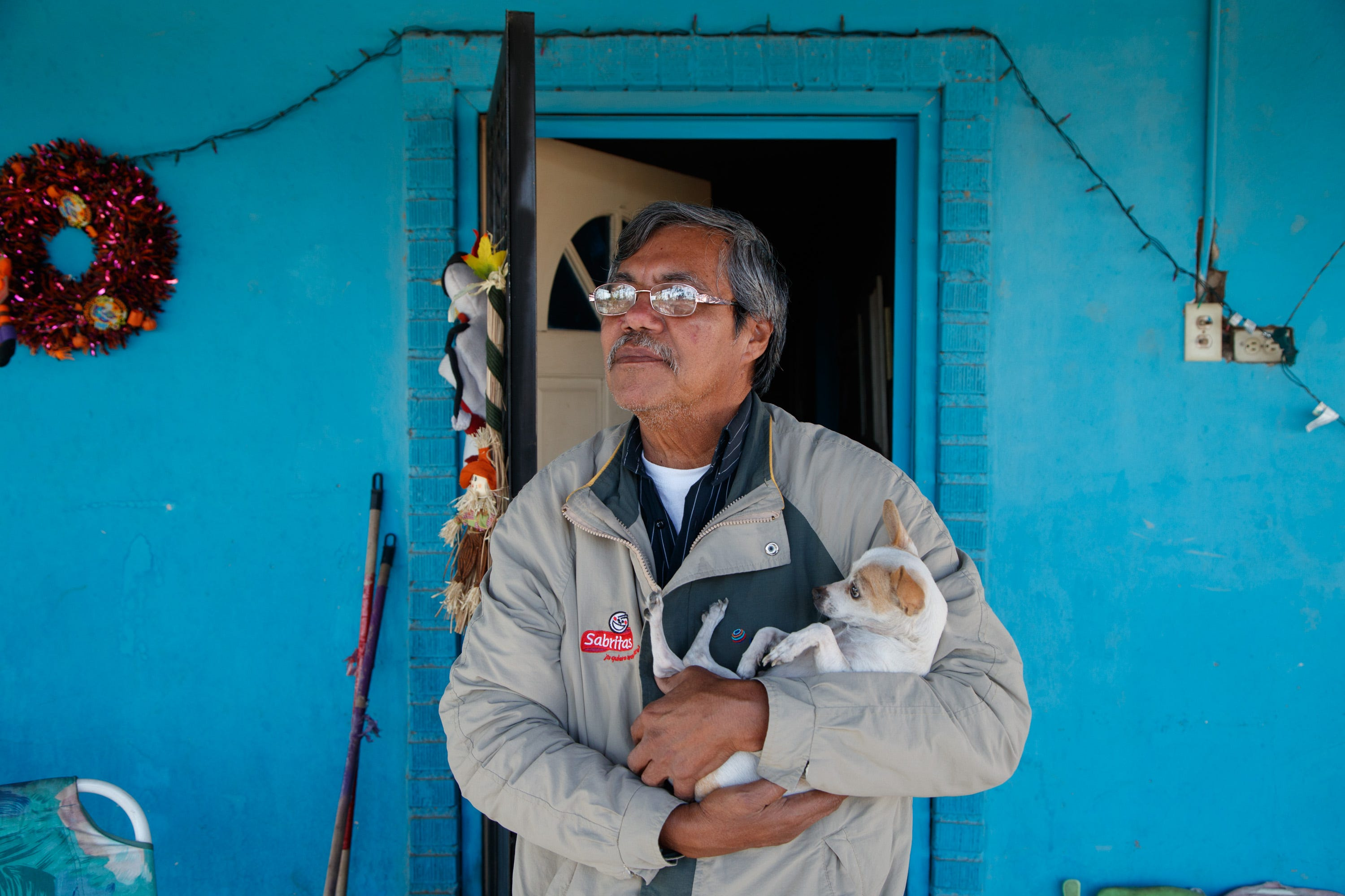 Julian López stands outside his home in a neighborhood next to several factories in Mexicali.