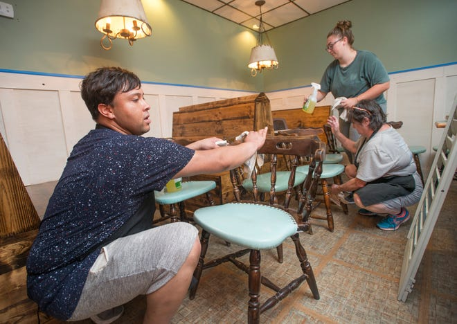 From left, Summer Rountree and Sharon Blackman, employees of the former Trigger's Seafood Restaurant, clean furniture Wednesday in preparation for the opening of the new Wolf Bay at Perdido restaurant in the same location.