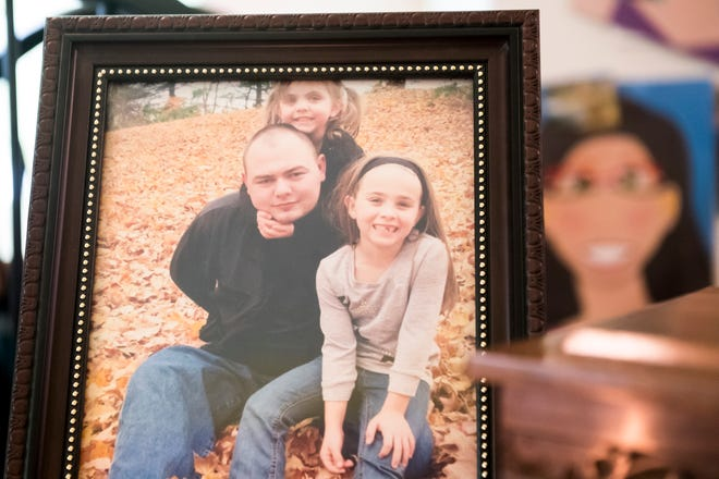 """A framed photo from 2016 of Zackery Rodkey with his daughter, Zoey (top) and his wife's daughter, Hailey, sits on a table at his mother's house in Heidelberg Township on Sept. 26, 2018. """"He always said he had two daughters ... He treated them both equally, there was no difference,"""" said Jessica Hooper, his wife."""