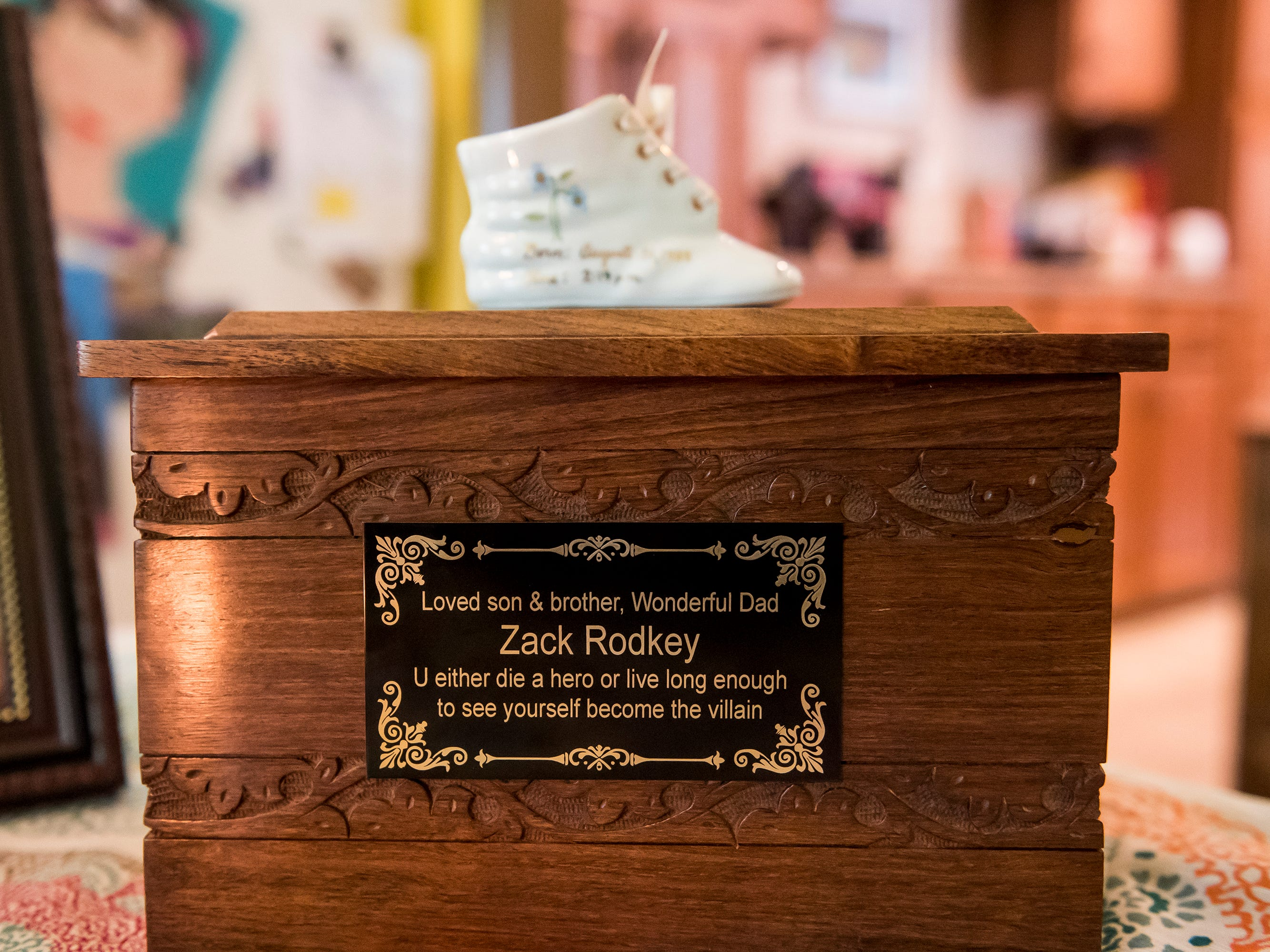 """A wooden urn containing the ashes of Zackery Rodkey sits on a table at his mother's house in Heidelberg Township September 26, 2018. The quote on the inscription is from the 2008 film """"The Dark Knight,"""" which was a favorite of Zack's."""