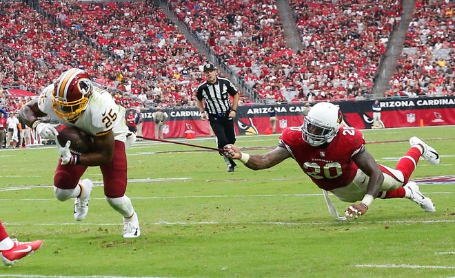 Arizona Cardinals linebacker Deone Bucannon (20) grabs Washington Redskins running back Chris Thompson (25) during the third quarter at State Farm Stadium in Glendale, Ariz. September 9. 2018.