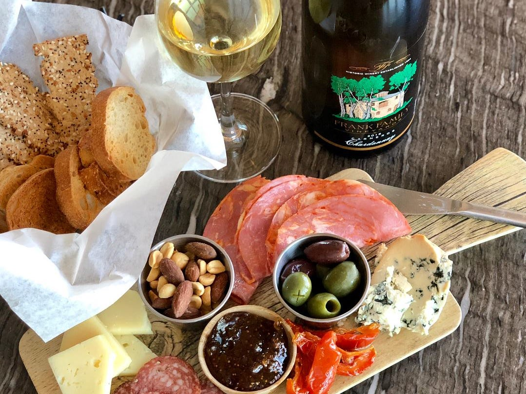 A cheese and meat board accompanied by wine and bread at Raven's View in Carefree.