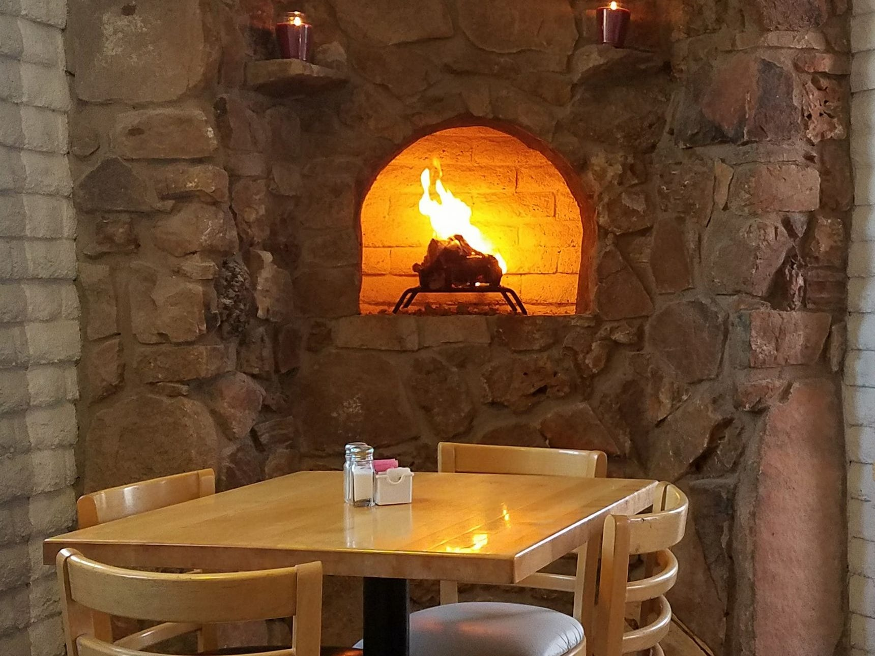 A cozy fireside table inside Sundial Garden Cafe in Carefree.