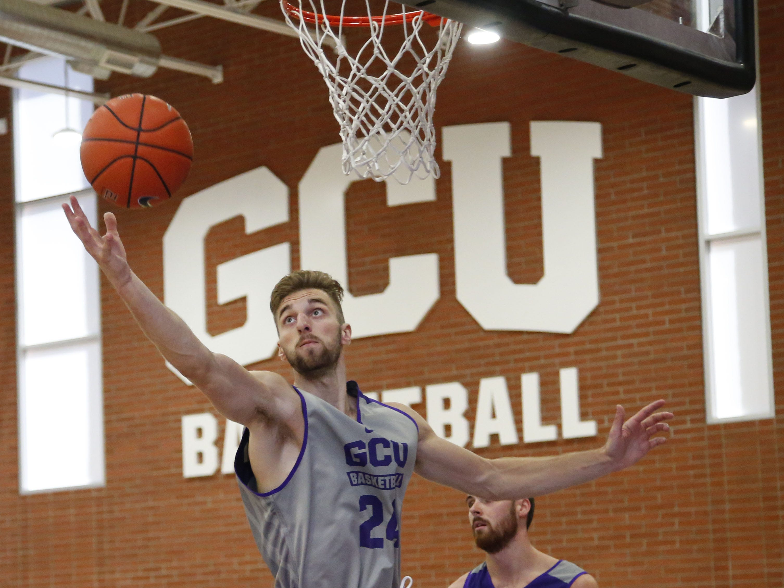 Grand Canyon University's Tim Finke, (24), reaches for the ball during practice in the gym in Phoenix on September 26,  2018.