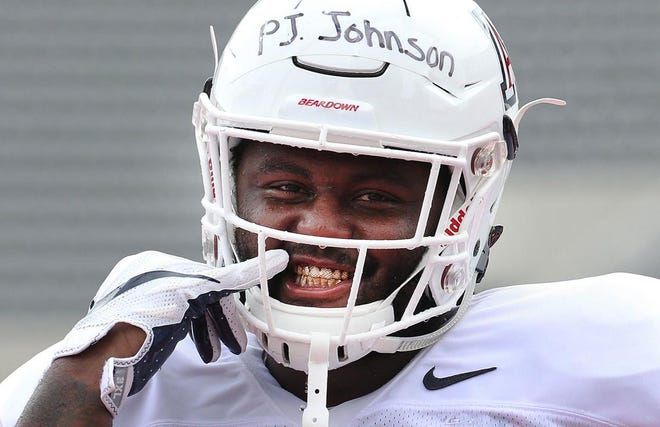Arizona Wildcats defensive tackle PJ Johnson shows off his gold grill during the University of Arizona Wildcats football team practice in Arizona Stadium on Aug. 8 in Tucson.