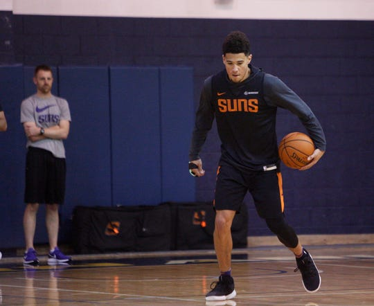 Suns guard Devin Booker works his left hand Wednesday during a training camp practice at Northern Arizona.