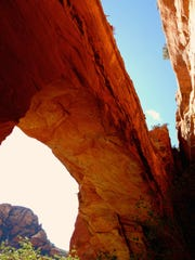 A natural arch hugs the cliff face in Fay Canyon in Sedona. A steep unmarked trail leads to the base of the span.