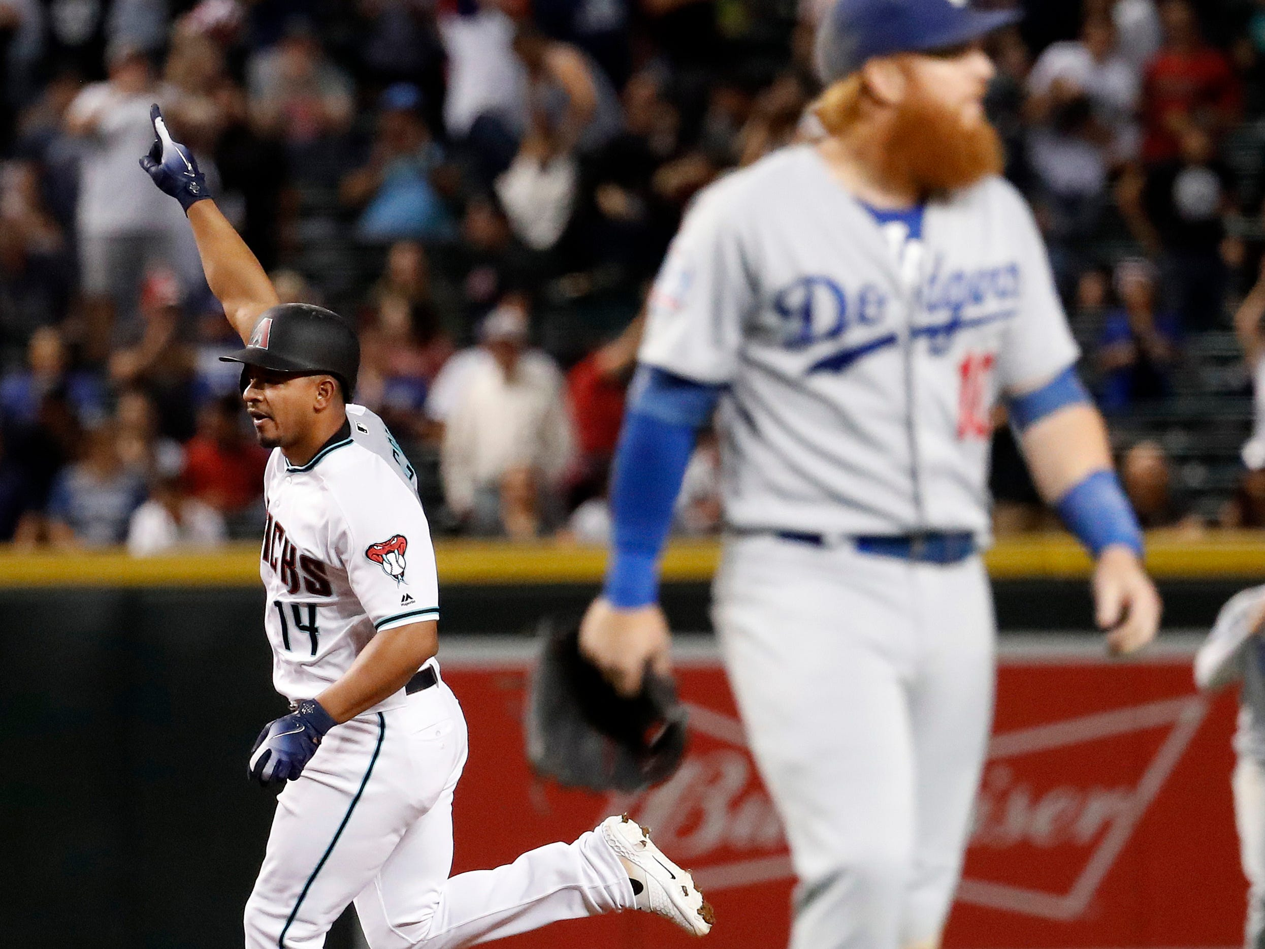 Arizona Diamondbacks' Eduardo Escobar (14) rounds the bases after hitting a walk-off home run as Los Angeles Dodgers third baseman Justin Turner leaves the field during the ninth inning of a baseball game, Tuesday, Sept. 25, 2018, in Phoenix. The Diamondbacks won 4-3.