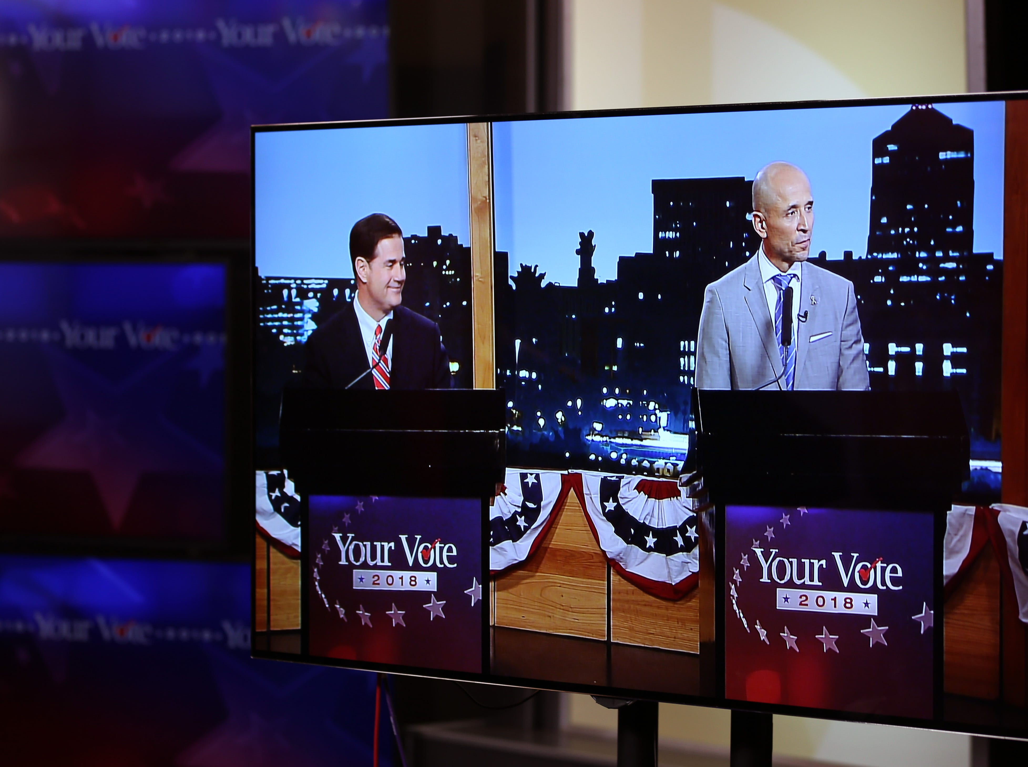 Gubernatorial candidates Republican Doug Ducey, left, and Democrat David Garcia, seen on monitors in an adjoining studio, wrap up a televised debate in the AZPM studios, Tuesday, Sept. 25, 2018, in Tucson.