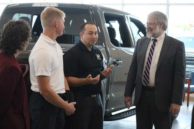 State Superintendent Paolo DeMaria, right, speaks with Grant Miller, of Baumann Ford Genoa, and his intern Spencer Segaard, a senior at Oak Harbor High School.