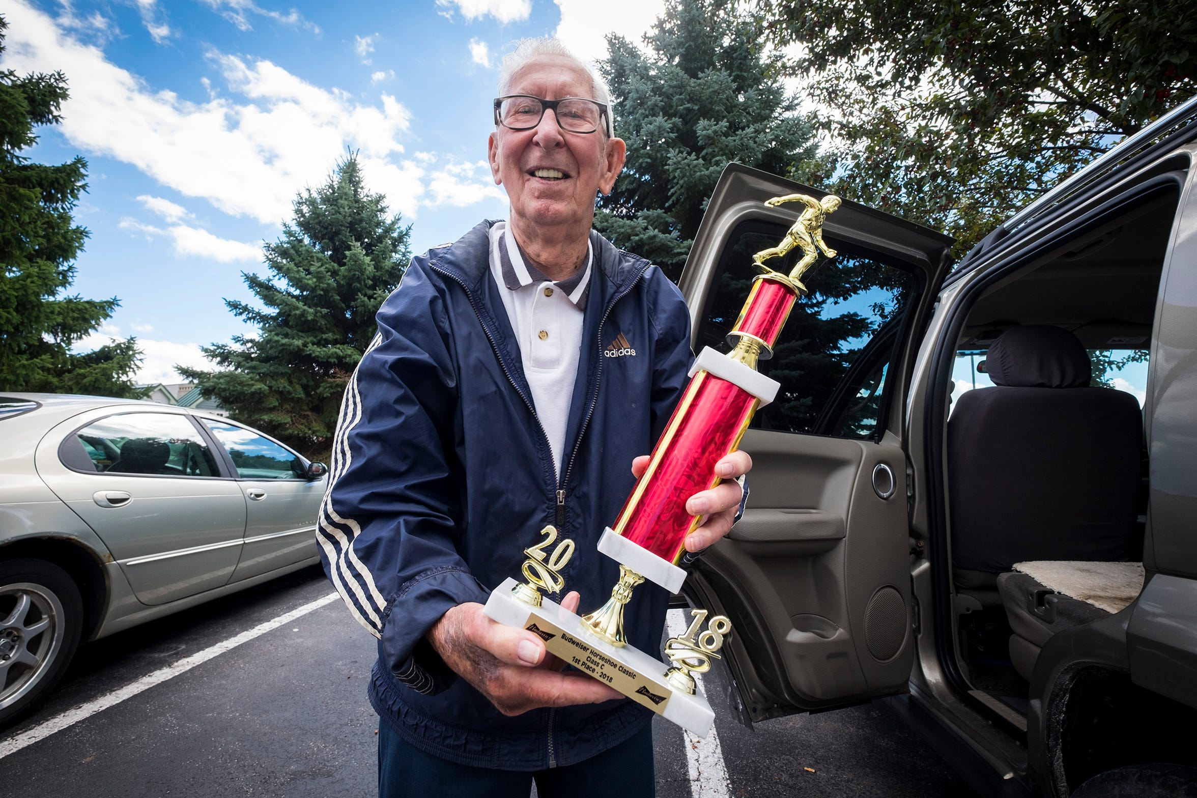 Bob Crorey, of China Township, shows off a trophy he won for placing first in the Budweiser Horseshoe Classic in 2018.
