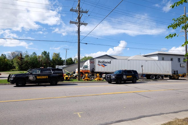 A live wire lays between the cab and trailer of a semi off 32nd Street in Port Huron Township Wednesday afternoon.