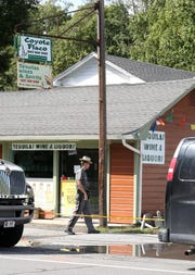 A New York State Trooper walks to the rear of a business on Route 82 in Stanfordville.