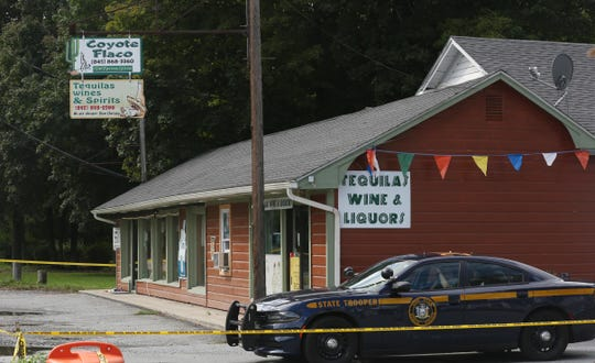A New York State Trooper sits in a car outside a business on Route 82 in Stanfordville.