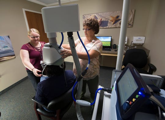 Brianna Fielding, left, LPN, and Susan Goetz, TMS coordinator, fit Casey Conner (seated) with the head gear portion of the Brainsway TMS therapy device on Wednesday, Septeember 26, 2018 at Keystone Behavorial Health, Chambersburg. The transcranial magnetic stimulation (TMS) device is designed to treat patients with depression.