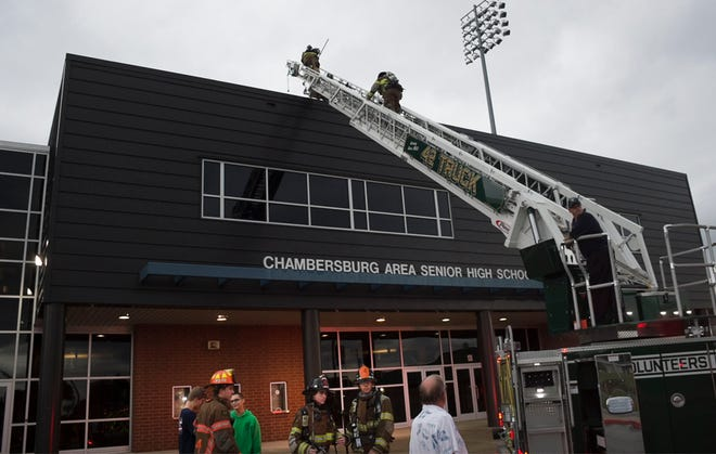Firefighters use a ladder truck to reach the roof of the gym area at Chambersburg Area Senior High School on Wednesday, September 26, 2018.