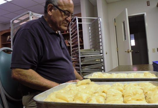 Steve Agapis, 73, looks down at two half sheet trays of baklava he and his wife, Bess Agapis, began preparing at 6 a.m. on Wednesday, September 26.