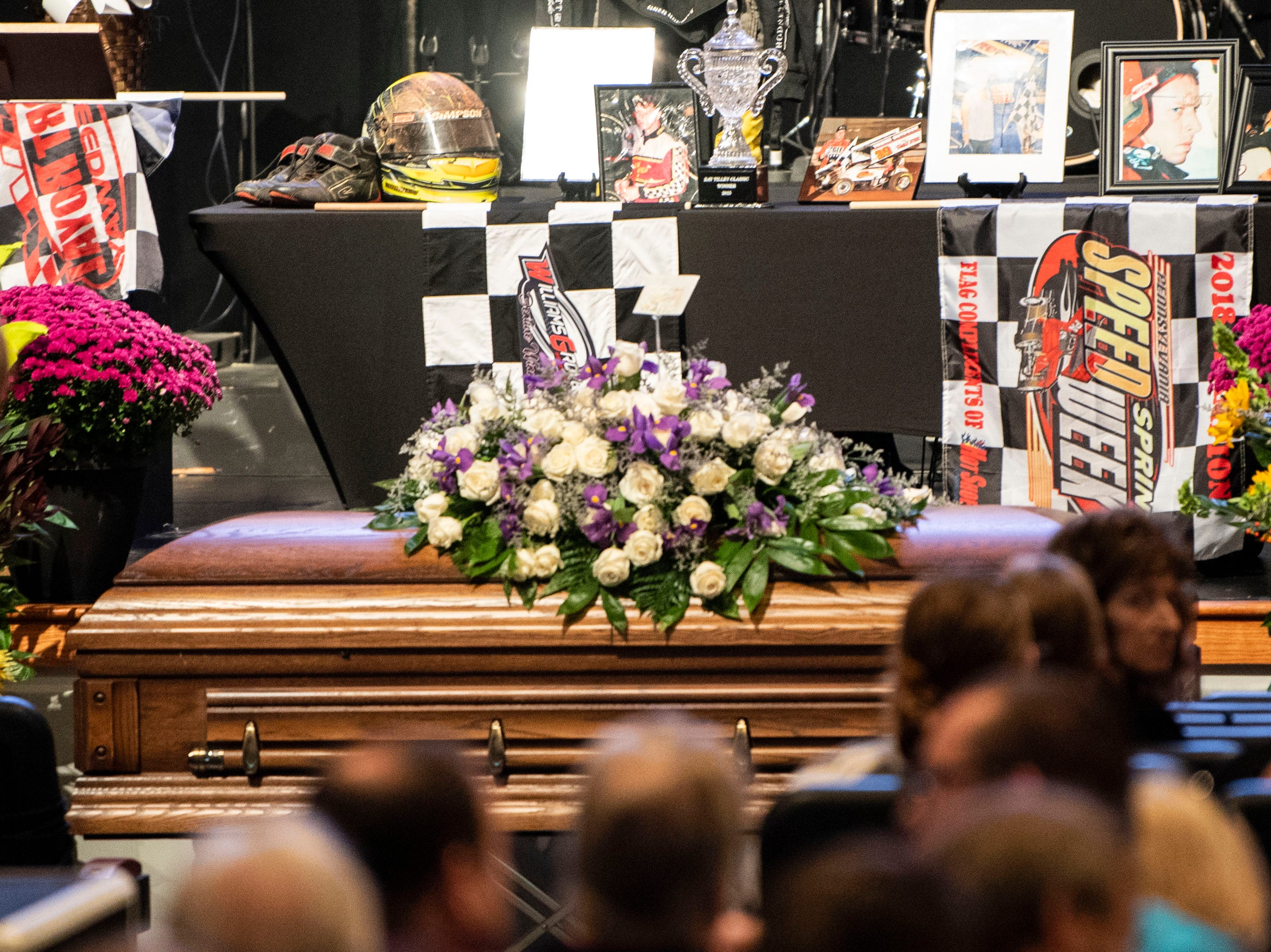 Flowers, checkered flags, pictures and trophies sit behind the casket of Greg Hodnett during his funeral on Wednesday, September 26, 2018. Hodnett, a local racing legend, died on September 20 at BAPS Motor Speedway.