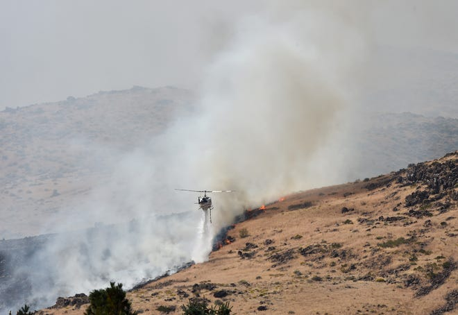 The Sheriff's helicopter drops water on the Shellbourne fire on in Reno on Sept. 26, 2018.