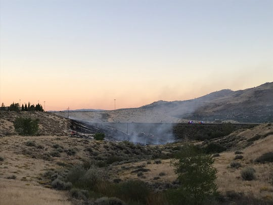 Crews fight a brush fire off Interstate 80 near Robb Drive.