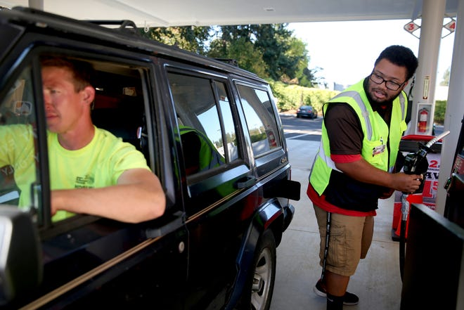 Matia White, a fuel clerk, pumps gas for Iggy Johnson on opening day of the South Salem Fred Meyer gas station on Wednesday, Sep. 26, 2018.