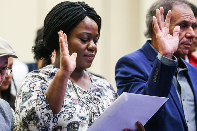 Christable Asare Ankwa raises her hand for the oath during the naturalization ceremony Wednesday, Sept. 26, 2018, at CJ Davidson Center at Angelo State University.