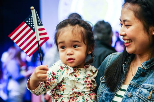Amy Voeyn, 2, holds a flag after Vicky Chanviyachat Eang received her naturalization certificate at the ceremony Wednesday, Sept. 26, 2018, at CJ Davidson Center at Angelo State University.