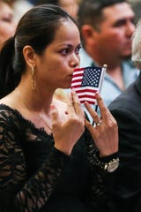 Victoria Becker kisses her flag during the naturalization ceremony Wednesday, Sept. 26, 2018, at CJ Davidson Center at Angelo State University.