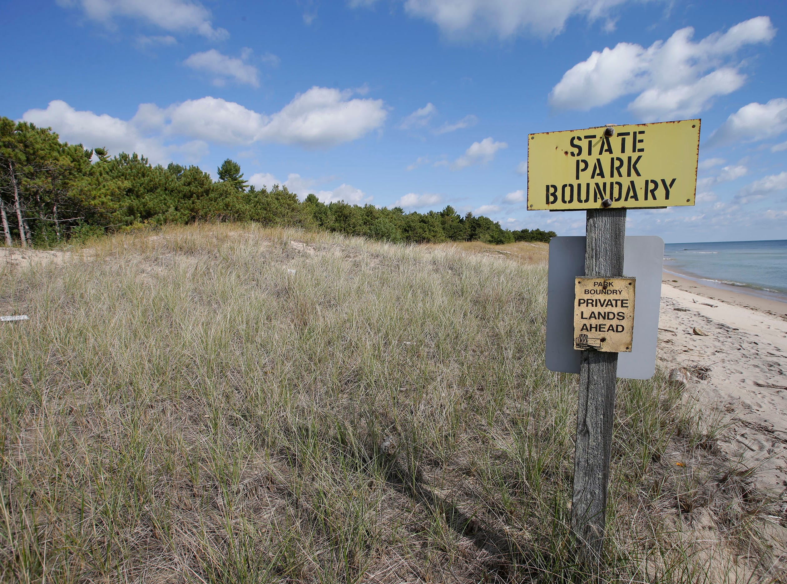 A sign marks where state park land ends and Kohler property begins at Kohler-Andrae Park, Wednesday September 26, 2018, in Sheboygan, Wis.