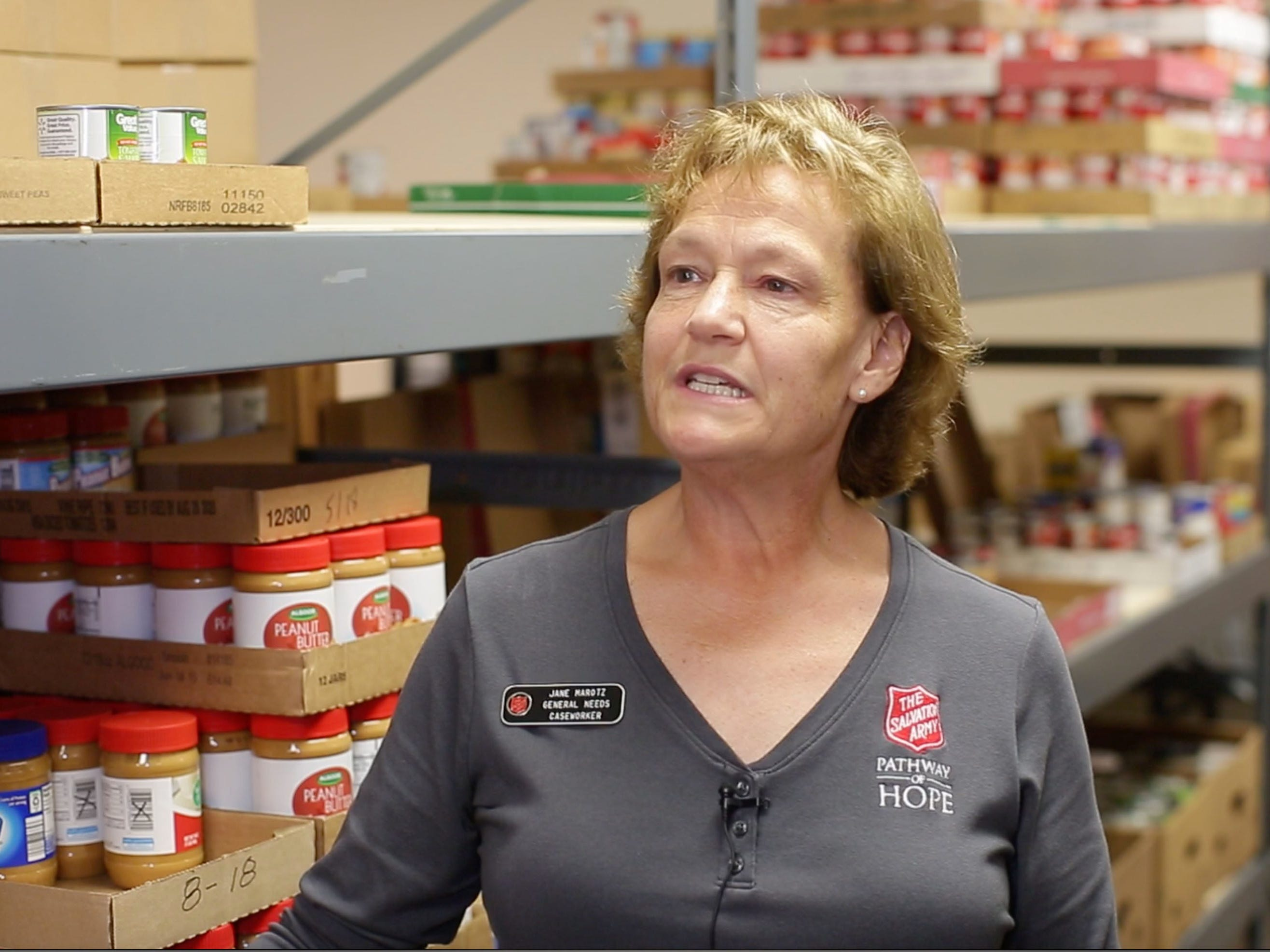 Salvation Army General Needs Case Worker Jane Marotz, speaks to the media while standing near the shelves in the food pantry at the facility, Thursday, September 20, 2018, in Sheboygan, Wis.