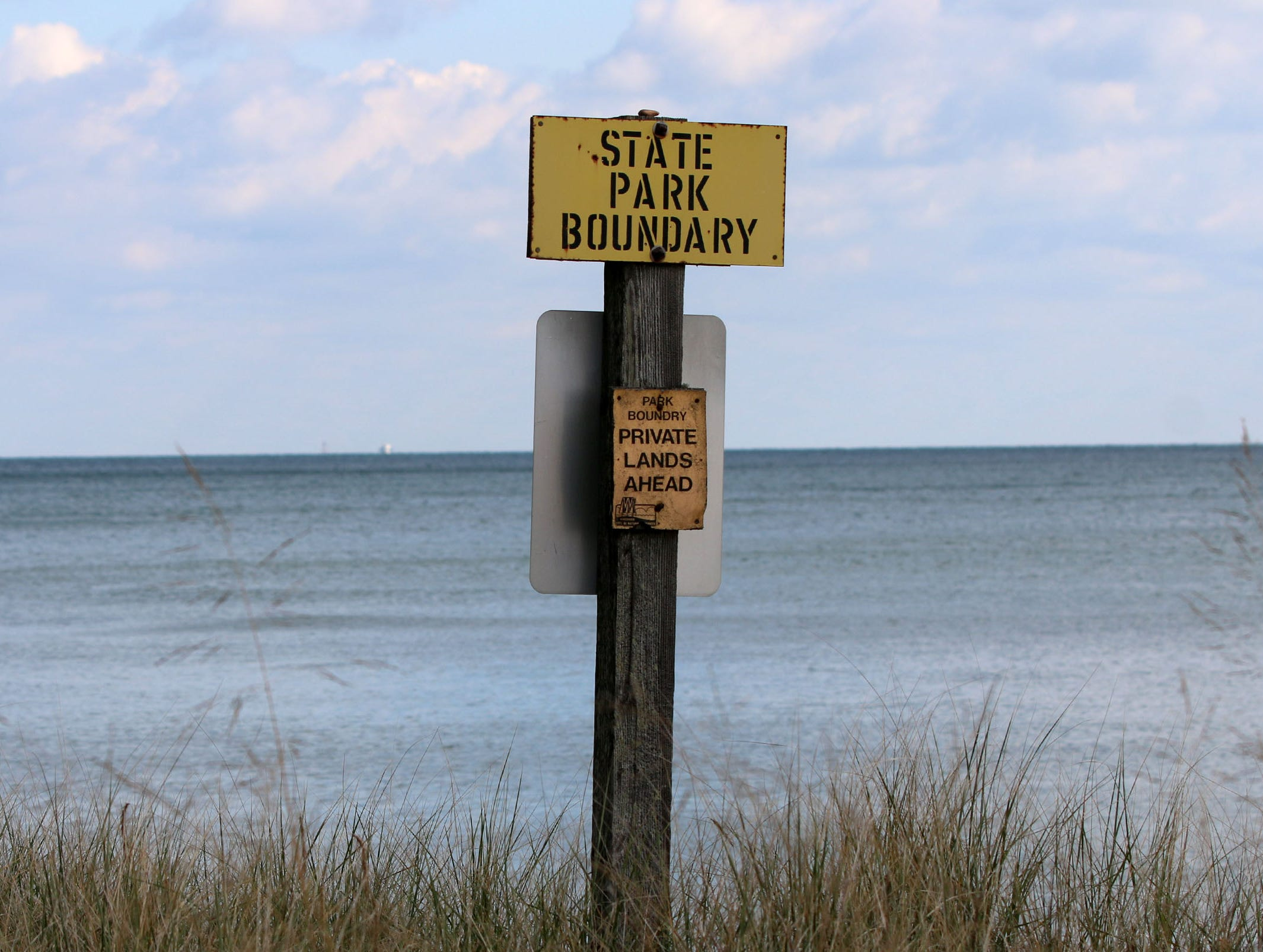A sign marks where state park land ends and Kohler property begins on the north end of Kohler-Andrae Park, Wednesday September 26, 2018, in Sheboygan, Wis.
