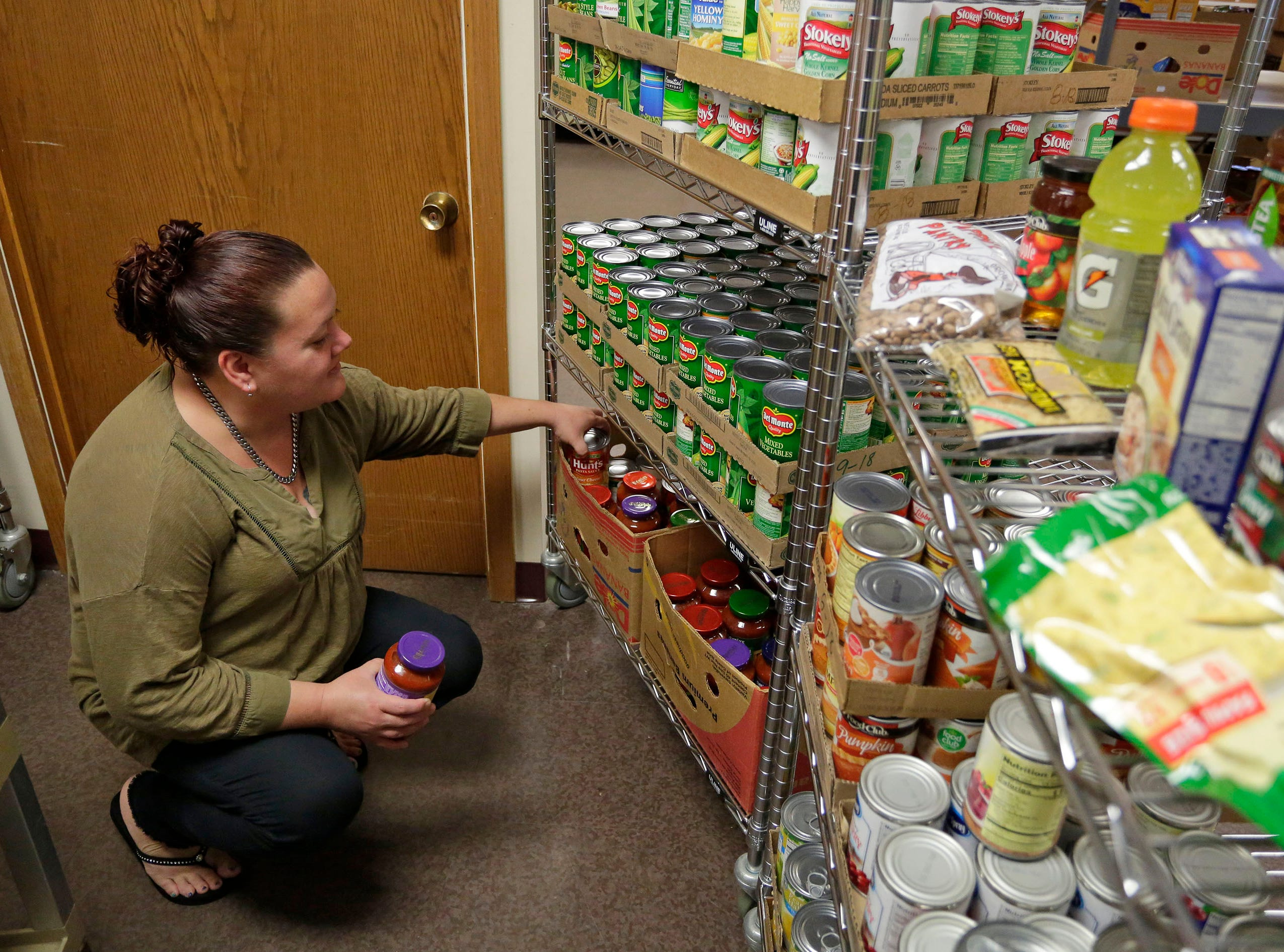Sheboygan Salvation Army food pantry recipient Rose Hauch, of Sheboygan, Wis., selects food, Thursday, September 20, 2018, in Sheboygan, Wis.