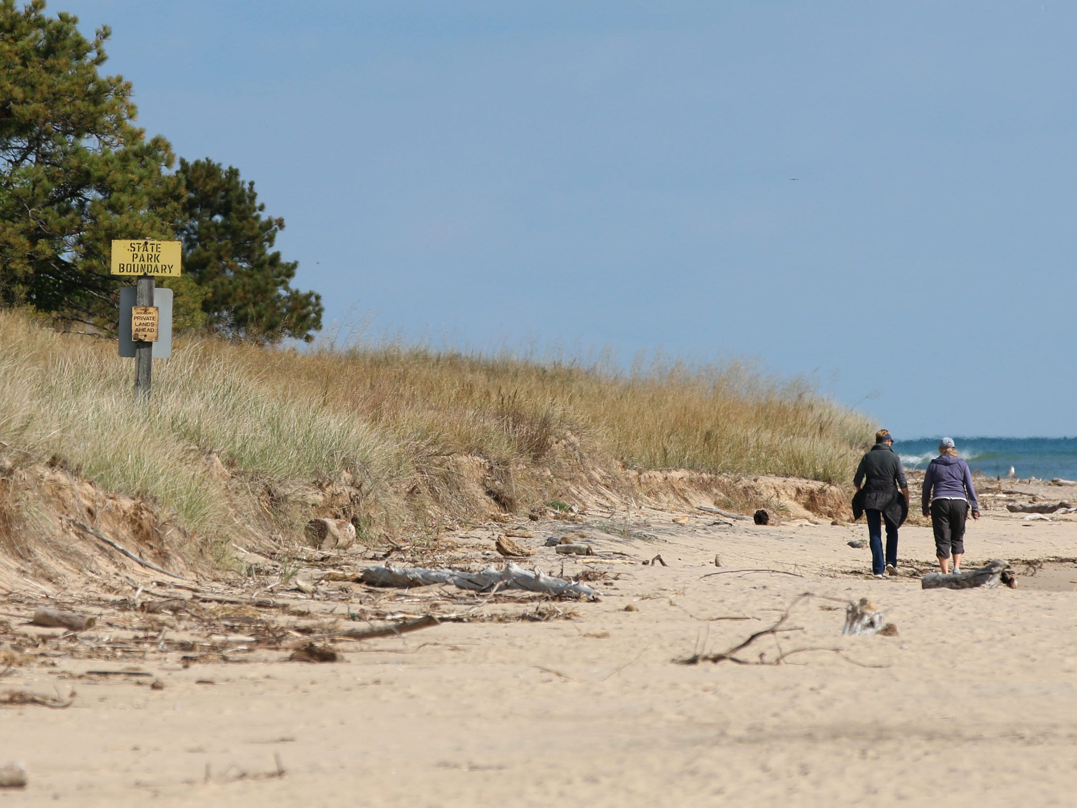 A couple walks by the Kohler-Andrae State Park and Kohler Company property line, Wednesday September 26, 2018, in Sheboygan, Wis.