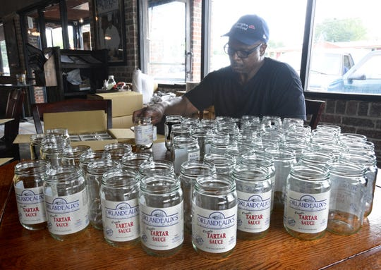 T.D. Lewis puts labels on Orlandeaux's Tatar Sauce jars before they are filled.