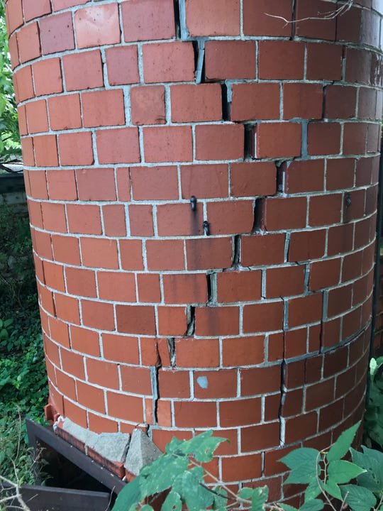 The base of the tall chimney at Elfindale Mansion is cracked and the chimney is, indeed crooked.